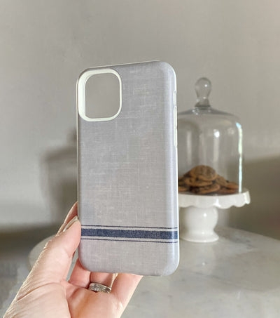french stripe on gray linen iphone 11 pro case held in front of cookie platter