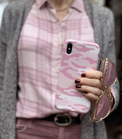 Pink camo phone case styled with sunglasses and plaid