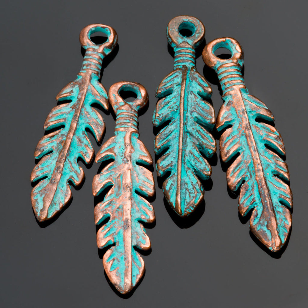 4 Green patina cast feather charms, 27 x 7mm