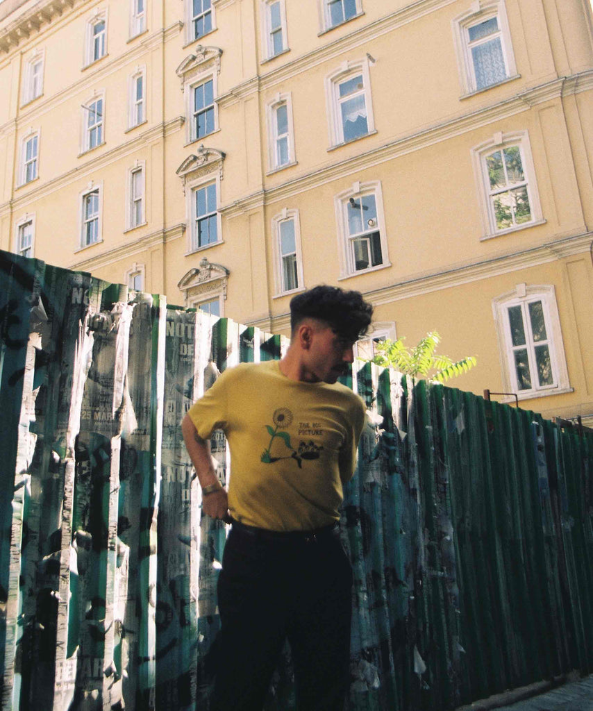 a man is wearing Aponia big picture yellow tshirt and standing in an alley while sun shines from one side