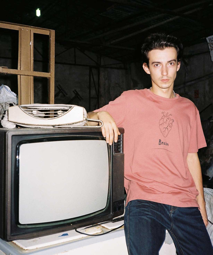 A guy is sitting next to an old tv and wearing Aponia brain graphic t-shirt in rose color. The graphic is a reall heart with underwritten of Brain.