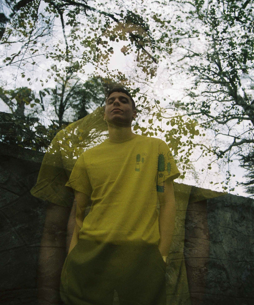 A man is wearing Aponia cactus yellow t-shirt and standing in a garden