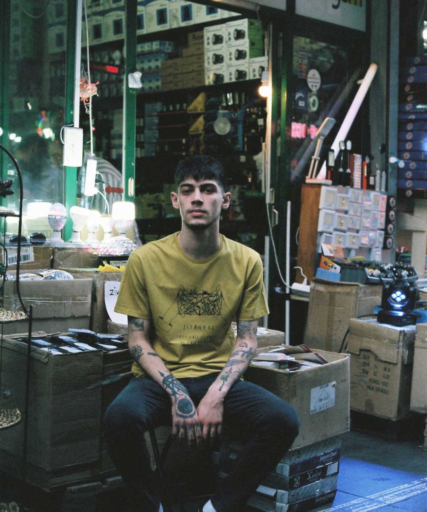 A guy is wearing Aponia cat's cradle yellow t-shirt and sitting in front of a store in bazaar