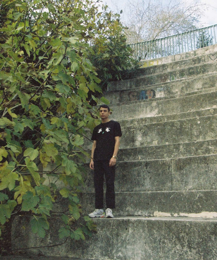 A guy standing on the stone stairs and wearing a black t-shirt with 2 astronauts holding arches