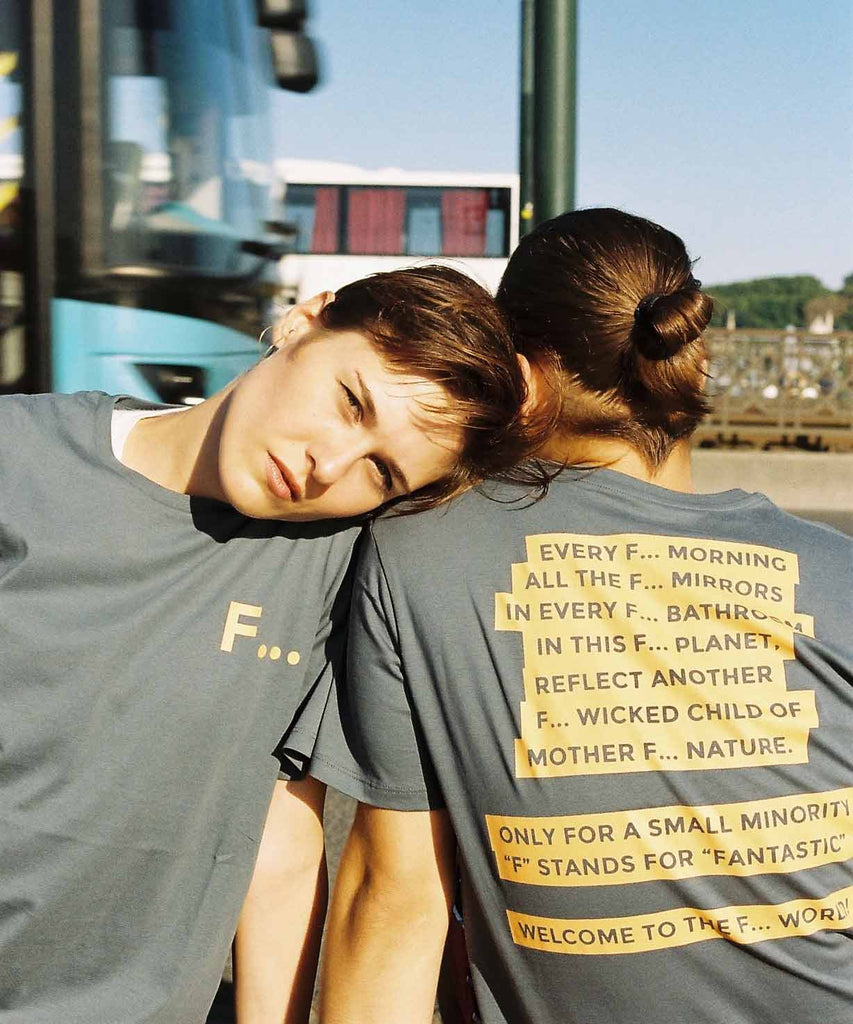 A guy and a girl sitting next to each other in street and wearing Aponia F world t-shirts