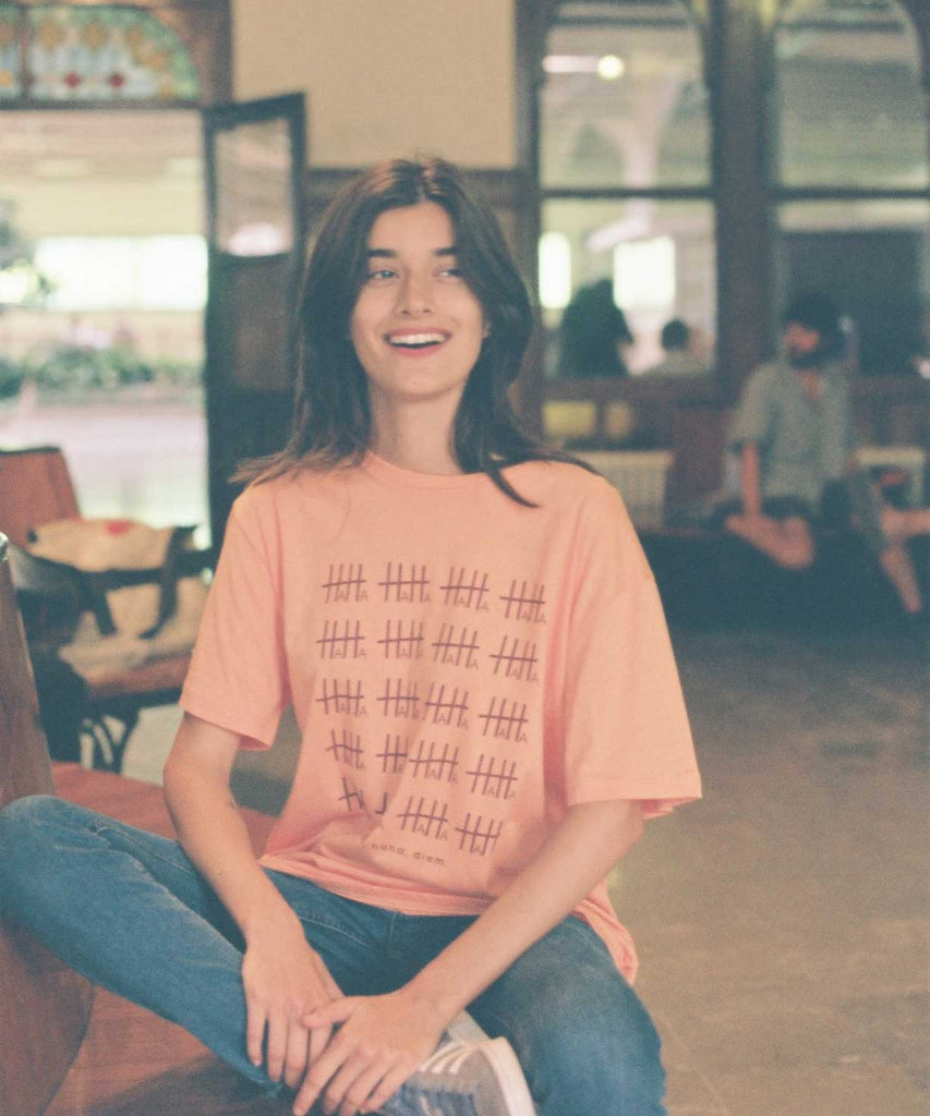 A girl who is smiling and wearing Aponia haha basic t-shirt in orange color