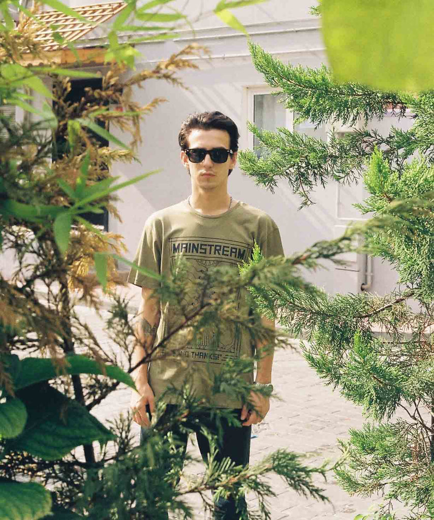 A guy with sunglasses is standing behind the bushes and wearing an olive t-shirt with graphic of hens, eggs and slogan of Mainstream? No thanks.