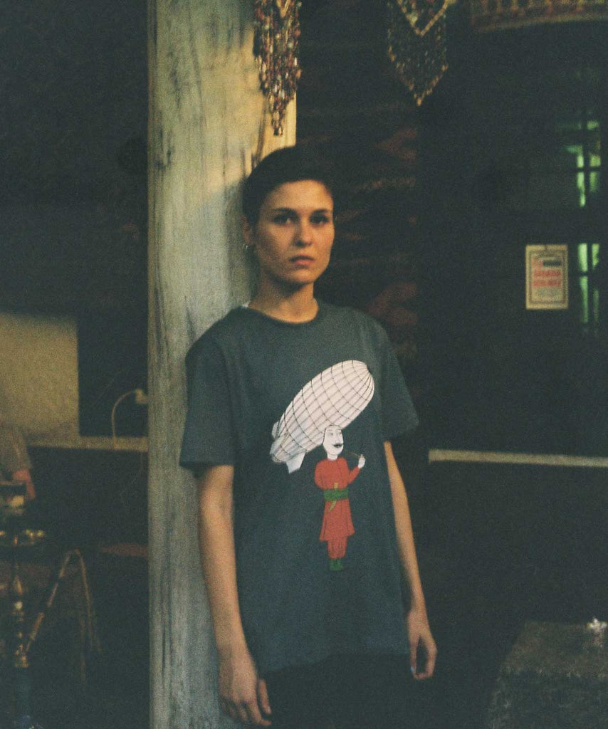 A girl is standing in front of wall and wearing a petrol basic t-shirt with graphic of a Turkish man who is smoking, while a big zeppelin is on his head