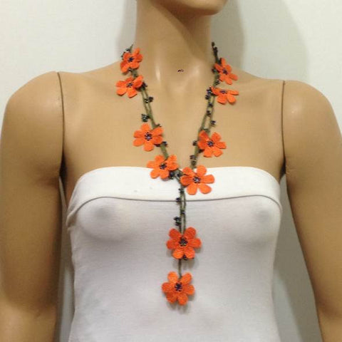 10.20.22 ORANGE OYA Flower Lariat Necklace with purplish black beads.