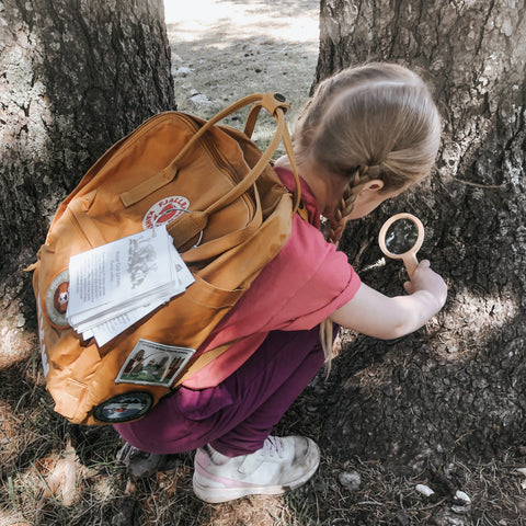 Girl exploring nature with magnifying glass