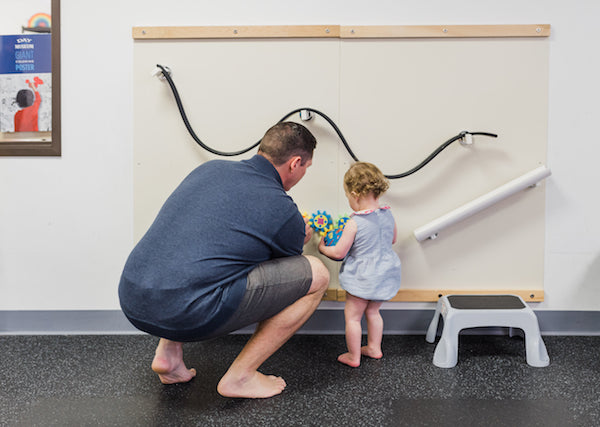 dad and daughter playing on the magnet wall