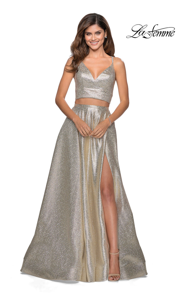 La Femme LF28618 long two piece gold prom flowy, simple dress. This 2 piece gown has a flowy skirt with a high slit & an open back v neckline top with straps. This metallic gold formal crop top & fitted skirt is perfect for 2020 prom dresses