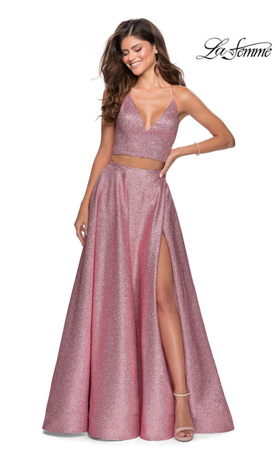 La Femme LF28618 long two piece pink prom flowy, simple dress. This 2 piece gown has a flowy skirt with a high slit & an open back v neckline top with straps. This metallic pink formal crop top & fitted skirt is perfect for 2020 prom dresses