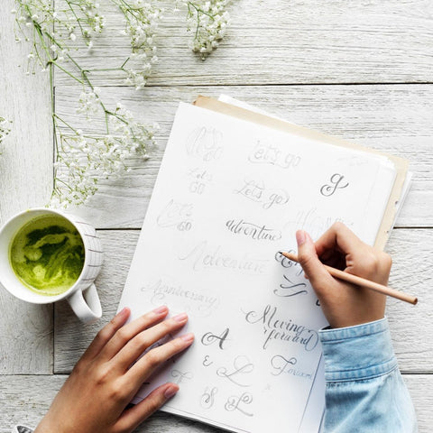 A woman's hands practicing calligraphy on a notebook; on the table are a mug of matcha and baby's breath.