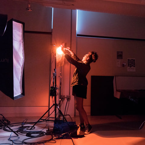A woman in a low-lit photography studio adjusting lighting.