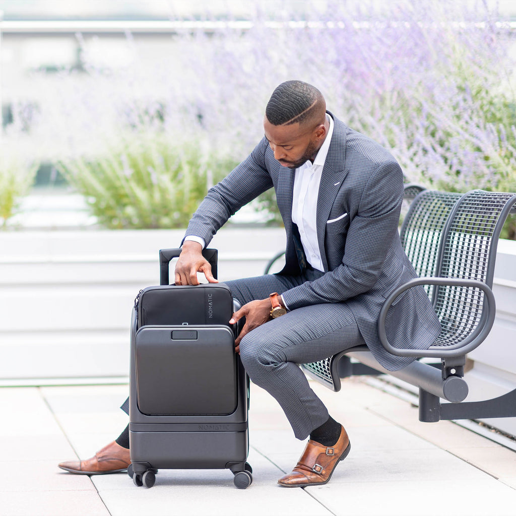 Gentleman putting laptop in Nomatic Carry-On Pro