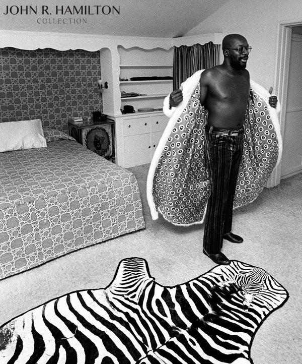 Isaac Hayes at home in his full-length white mink coat.  Los Angeles.   [1971]