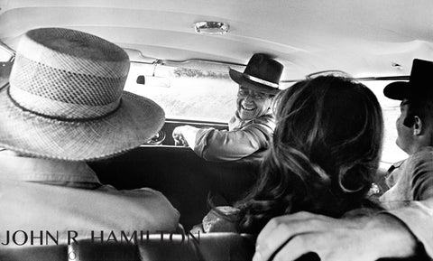 John Wayne in car with Howard Hawks, Michele Carey, and James Caan on the set of El Dorado