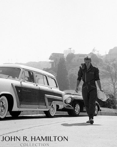 Steve McQueen in racing gear walking in the hills of Los Angeles, CA.  1960