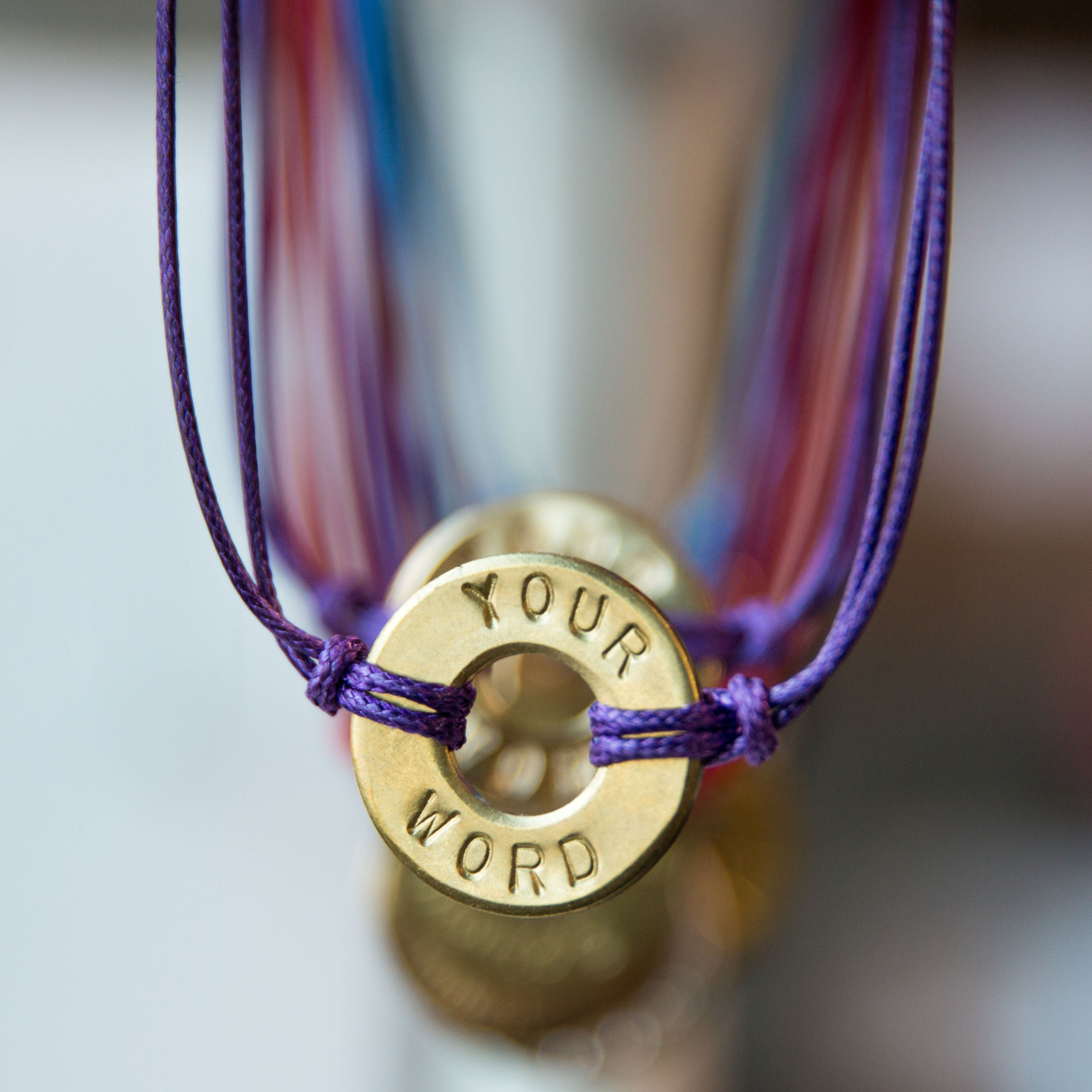 A close-up of MyIntent Custom Classic Bracelet Purple String with Brass Token
