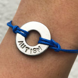 Girl wearing her MyIntent Custom Classic Bracelet Awareness Edition Blue string with the word AUTISM