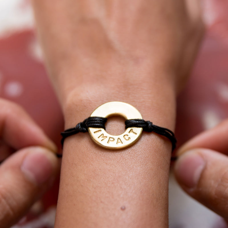 Someone placing a MyIntent Custom Twist black string Bracelet Brass token with word IMPACT