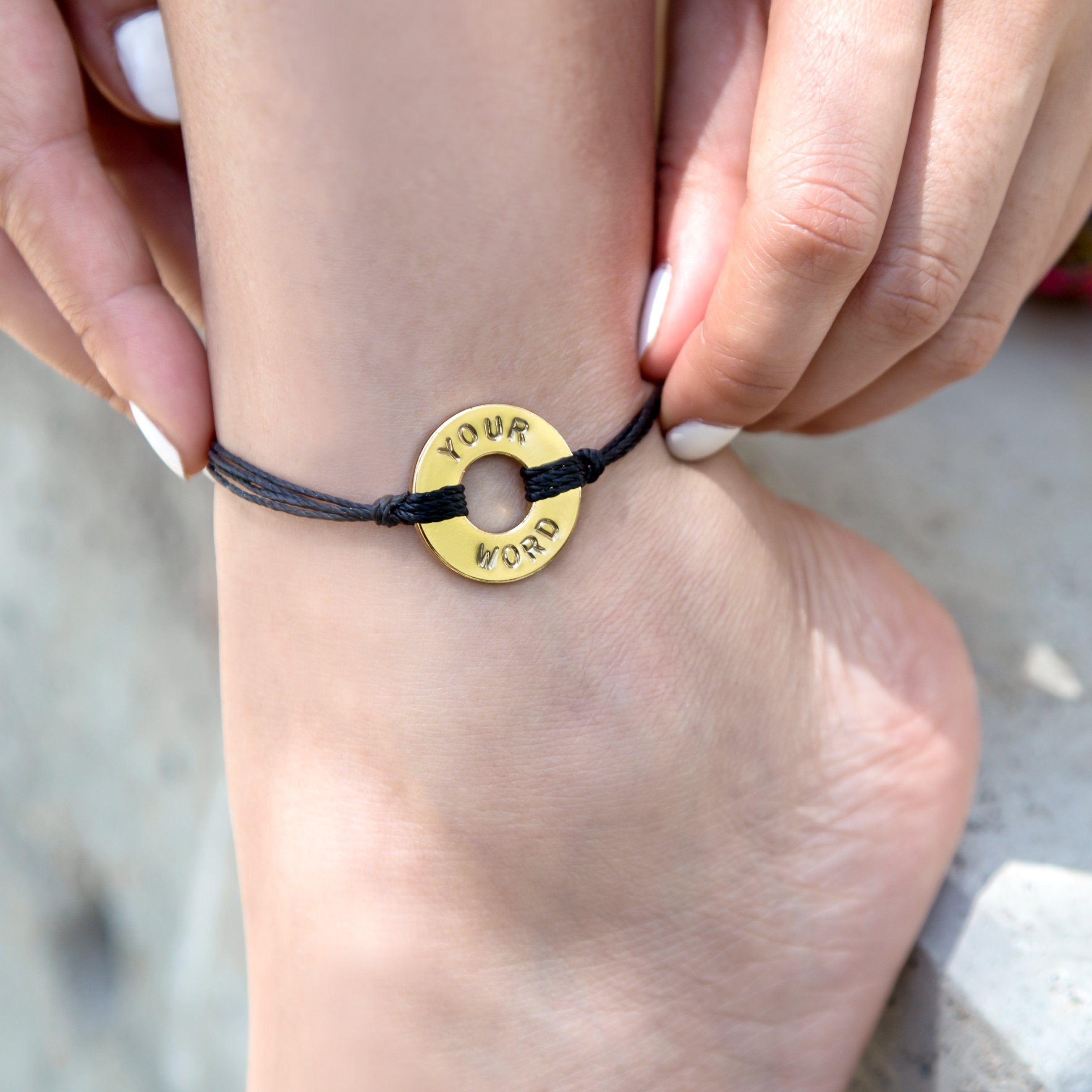A girl adjusting her MyIntent Refill Twist Anklet Black String with Gold Token