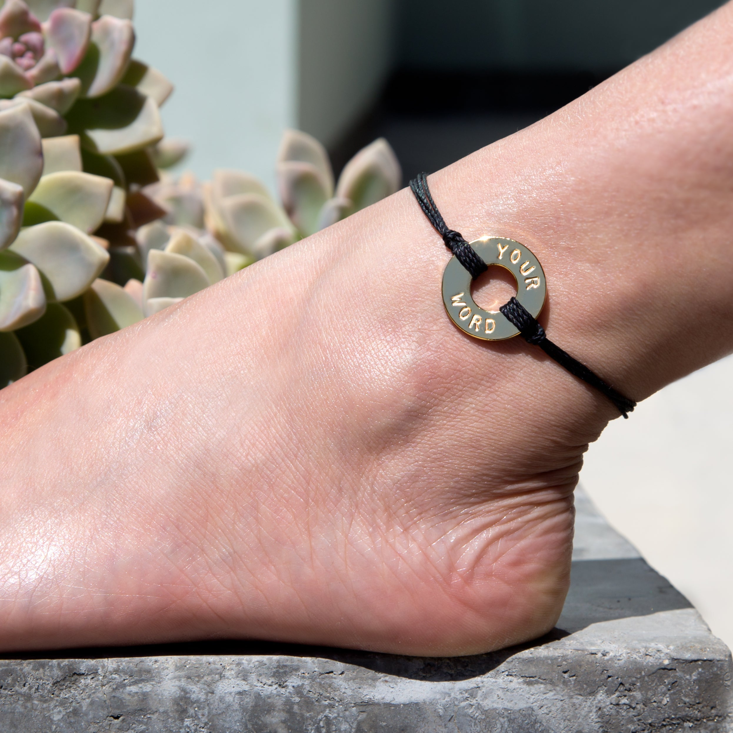 A girl showing her MyIntent Custom Twist Anklet Black String with Gold Token