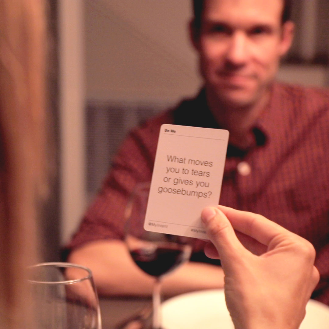 A woman reading a question from a MyIntent Question card at the dinner table