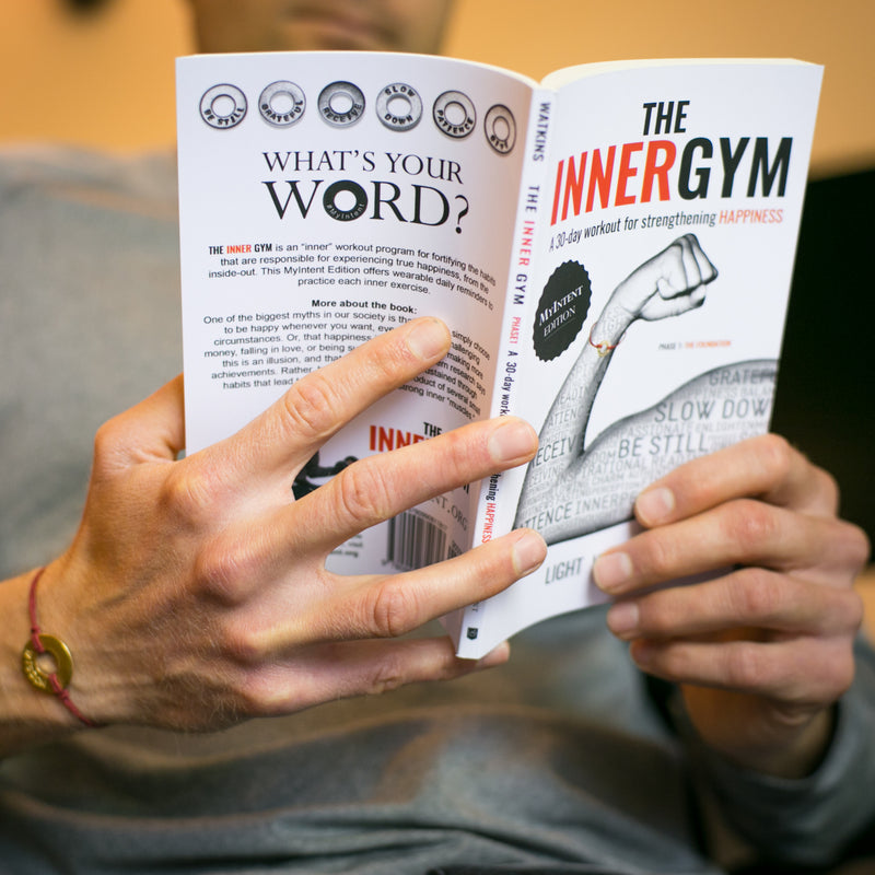 A person reading The Inner Gym book while wearing their MyIntent bracelet