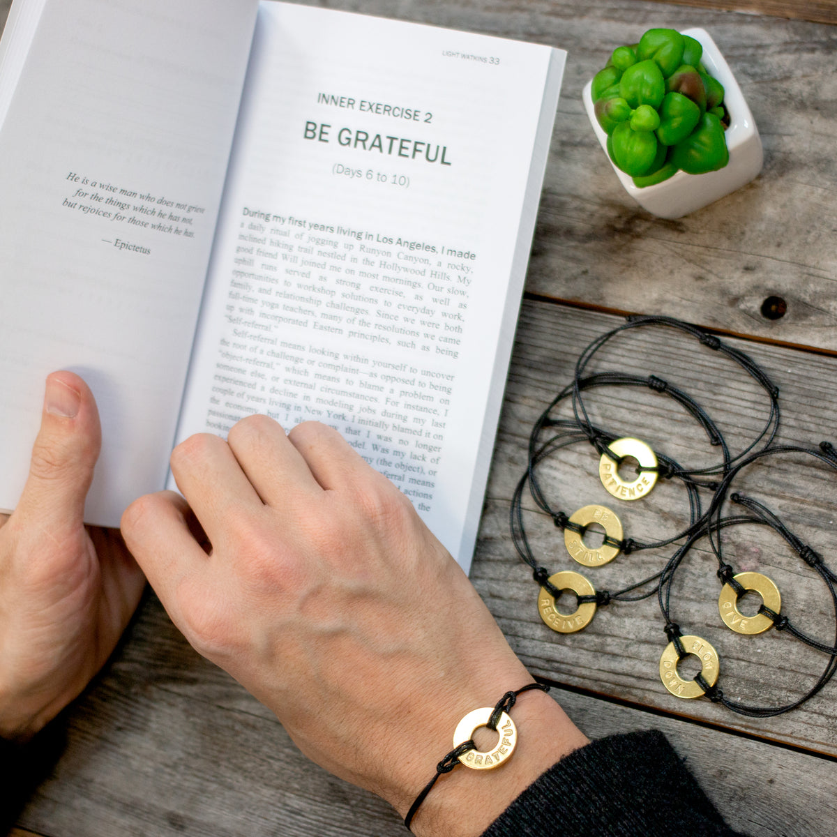 A person reading The Inner Gym book while wearing their MyIntent classic black bracelet