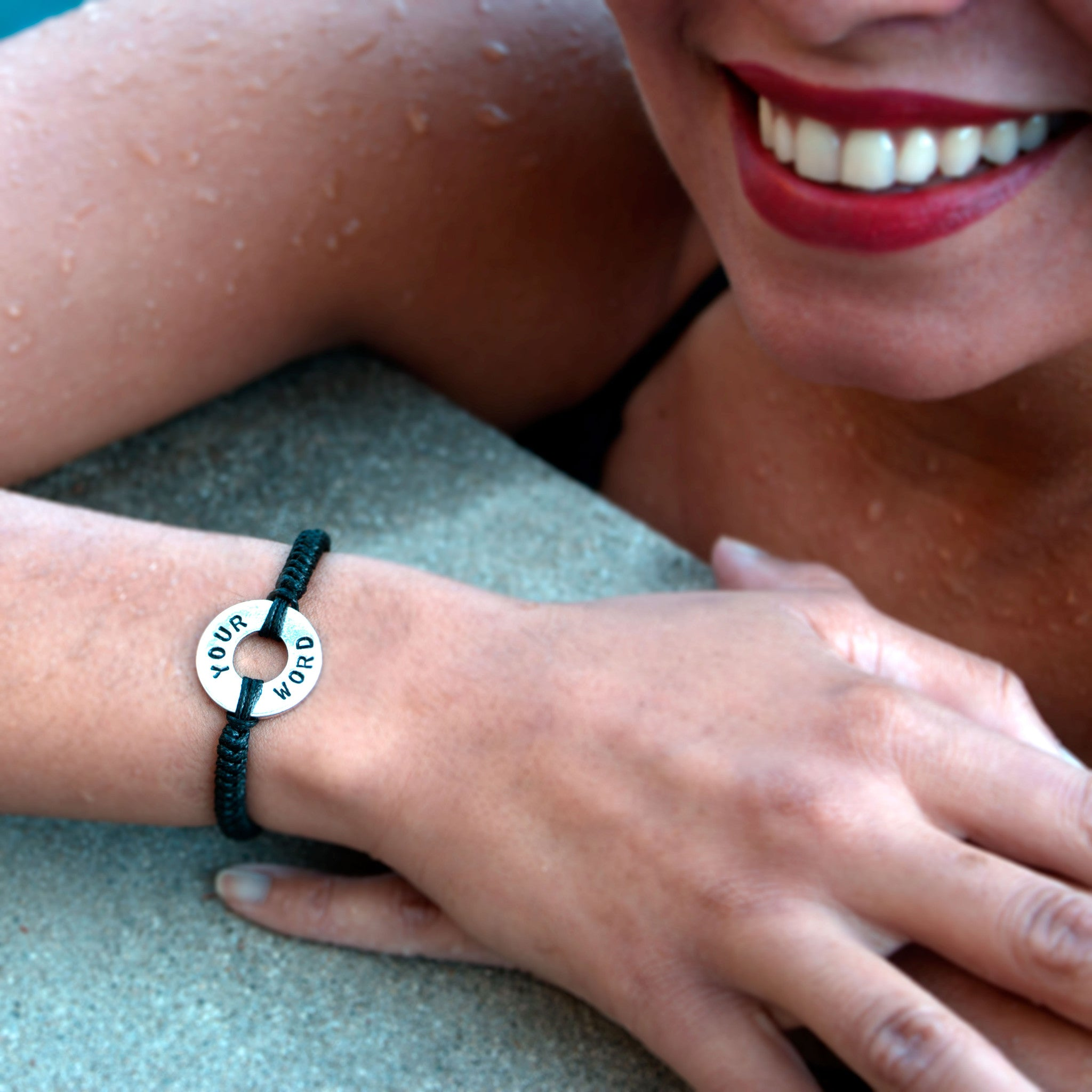 A girl wearing her MyIntent Custom Round Bracelet Silver Token with Black String