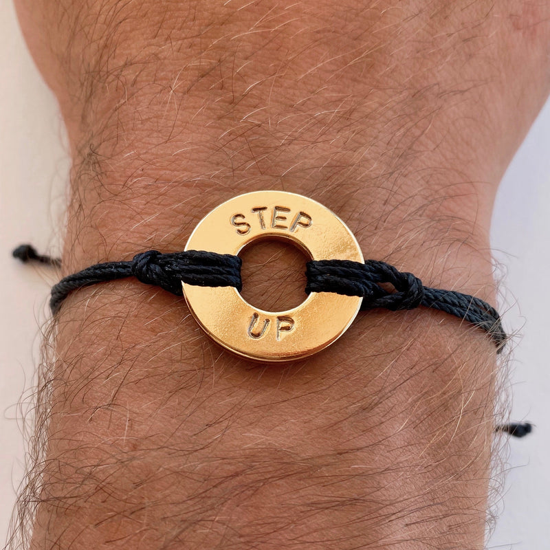 Person wearing MyIntent Custom Twist Bracelet Black String Gold Plated Token with the words STEP UP