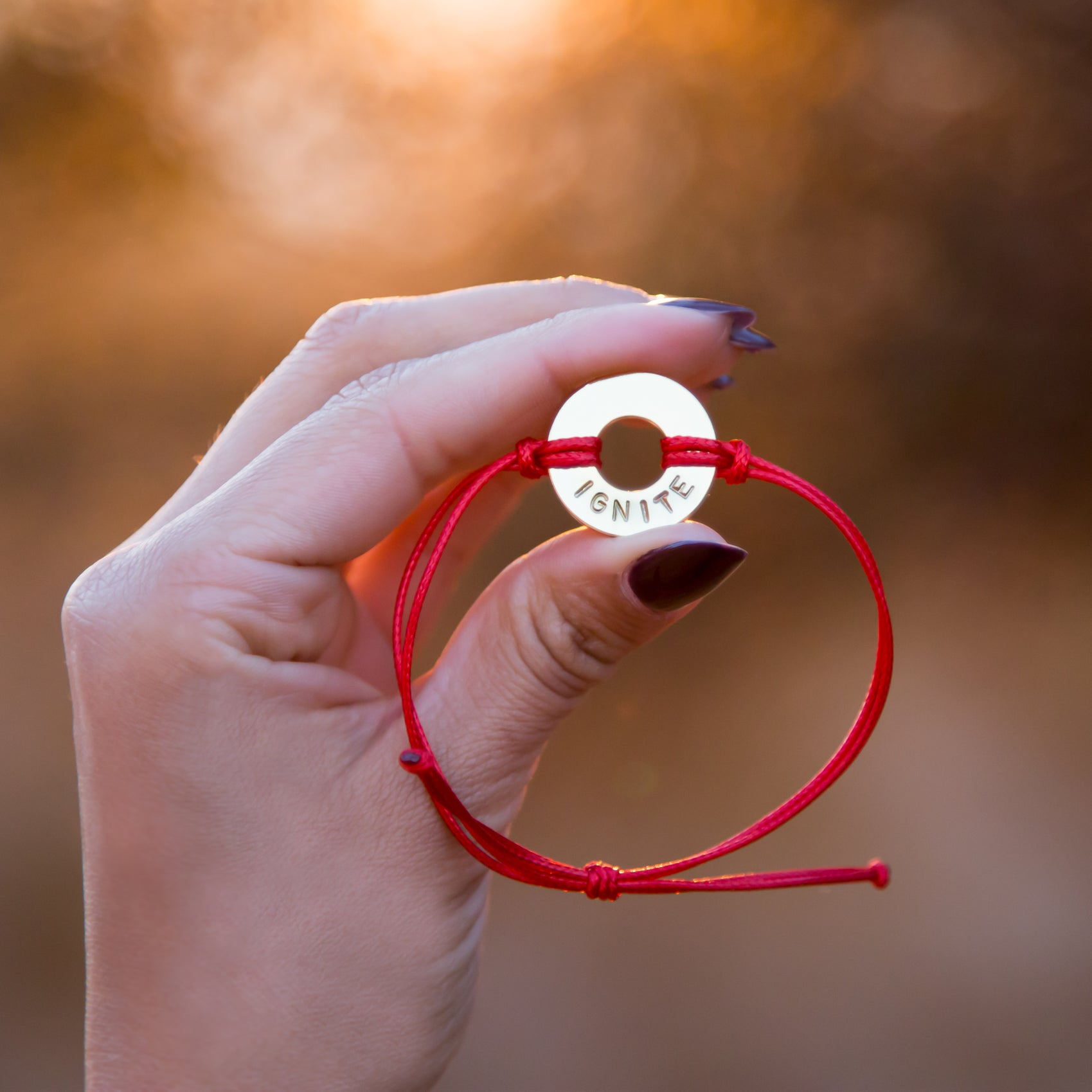 Person holding their MyIntent Custom Classic Bracelet Red String Nickel Token with word IGNITE