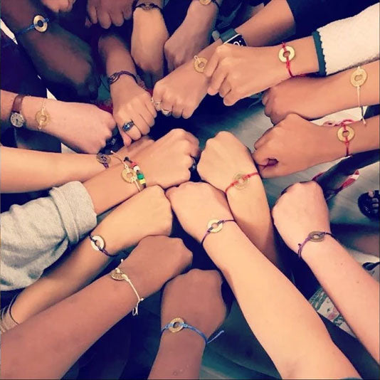 A group of people extending their wrists to show their own unique MyIntent bracelets in different color styles and words