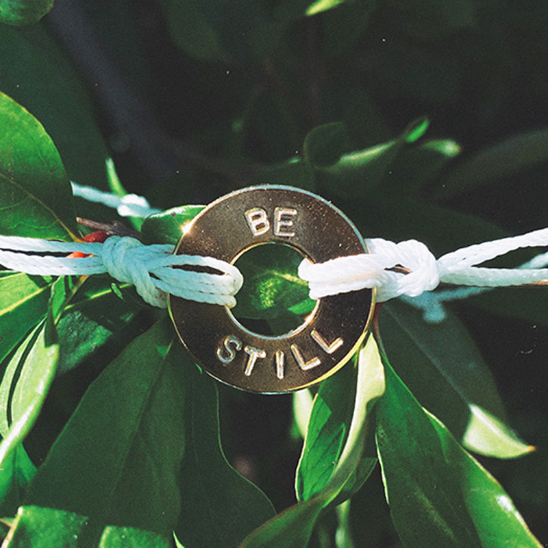 A MyIntent Custom Twist White Bracelet Gold Token with the words BE STILL