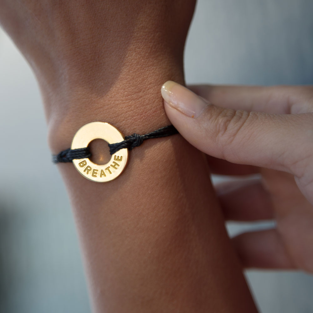 A woman adjusting her MyIntent Classic Black Bracelet with the word BREATHE