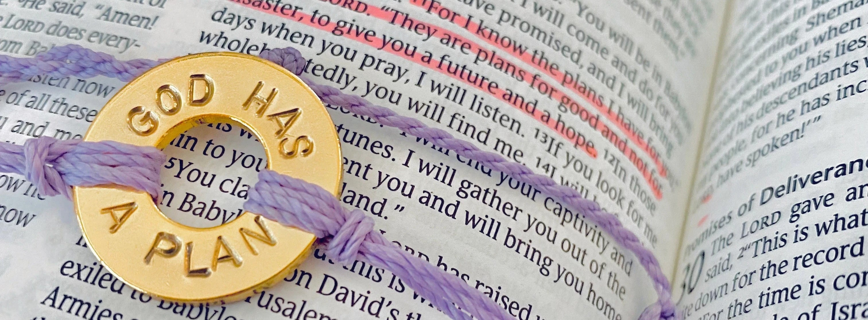 A MyIntent Custom Twist Lavender Bracelet Gold Token placed on a Bible with the words GOD HAS A PLAN