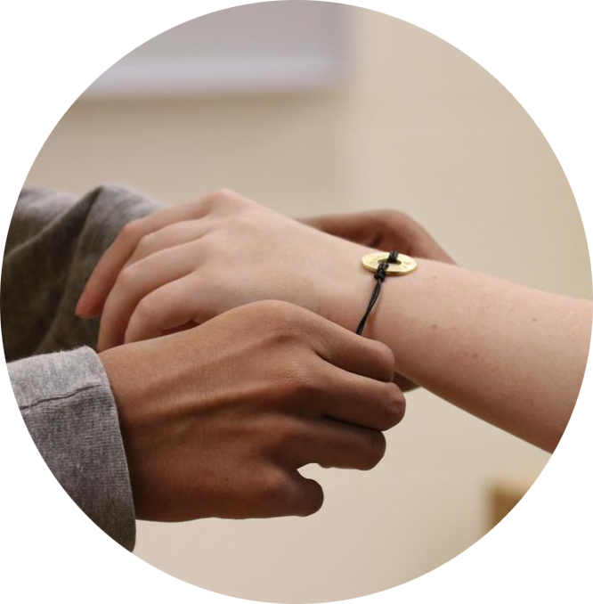 A person gifting a MyIntent bracelet to another person