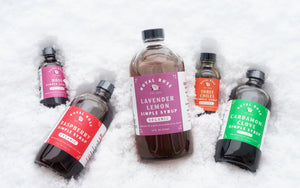 Royal Rose Organic Simple Syrups, Rose, Raspberry, Lavender Lemon, Three Chile and Cardamom-Clove displayed in fresh Maine snowfall.