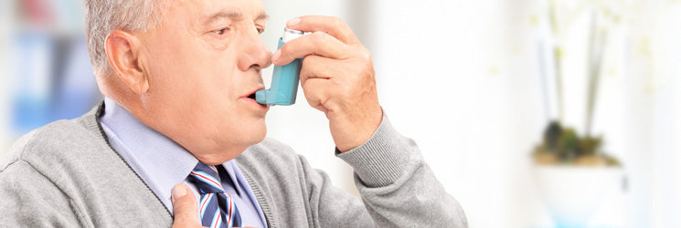 Older Man using an Inhaler.