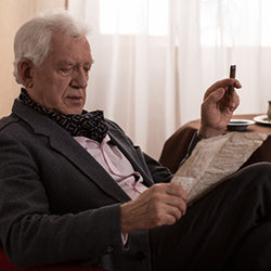 Old man in a suit sitting down, reading a newspaper, and smoking a cigar