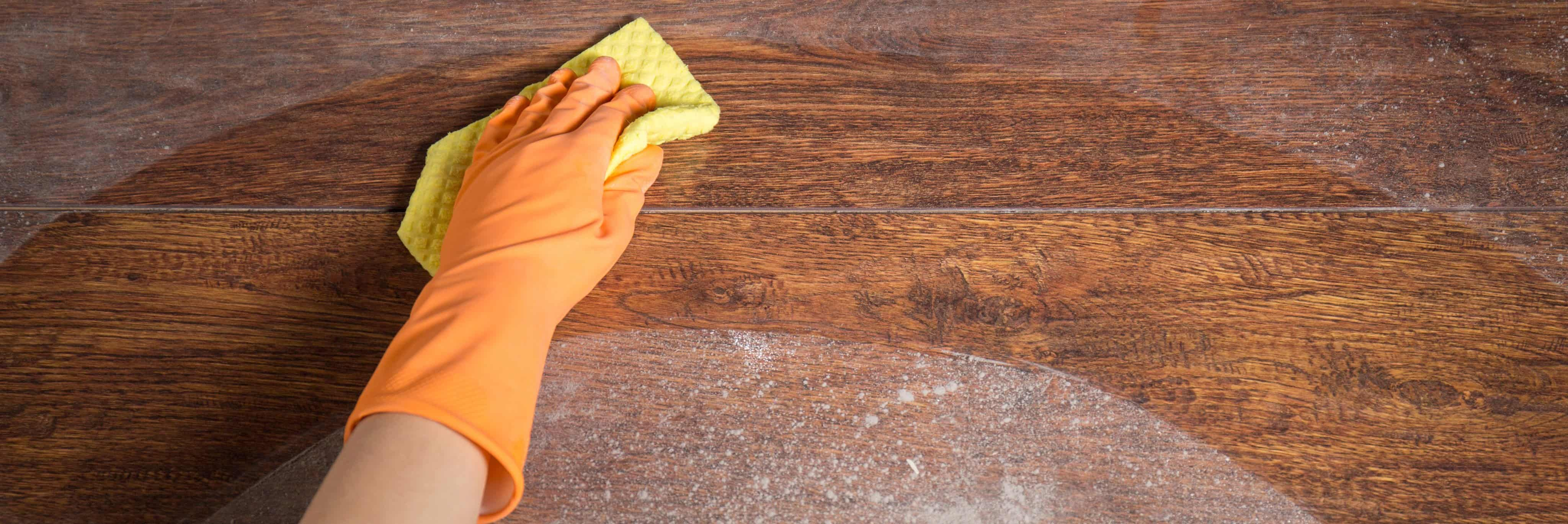 Hand wearing an orange cleaning glove using a yellow sponge to wipe away dust from a brown wooden surface