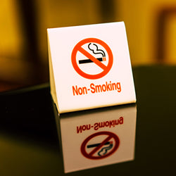 Small white Non-Smoking sign on a reflective table