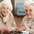 two elderly women playing dominos