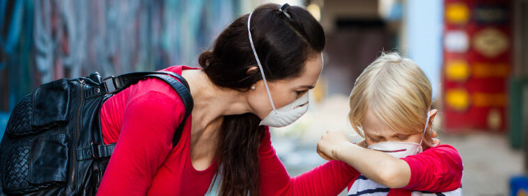 mother comforts coughing son as both wear pollution masks