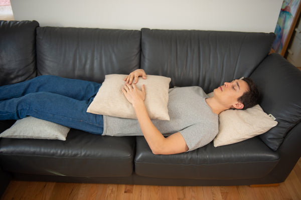 Man using a supportive buckwheat sofa cushion