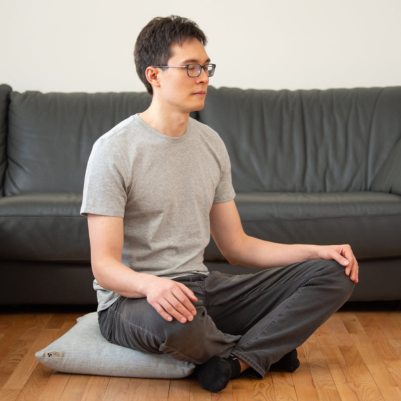 Man using a supportive buckwheat sofa cushion as a meditation cushion