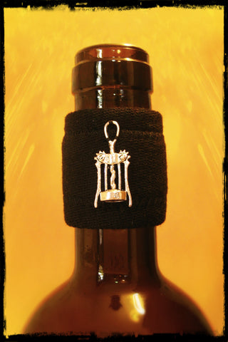 Wine accessory drip stopper band with silver corkscrew pendant