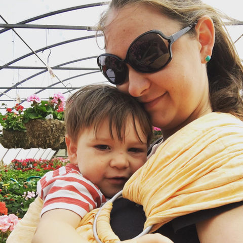 Image of a white woman wearing oversized black sunglasses.  She stands inside a very large greenhouse wearing her baby in a yellow ring sling.
